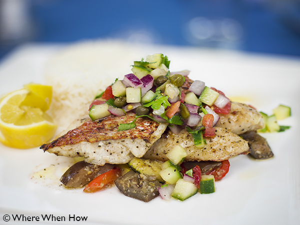 A photograph of Fresh locally caught Snapper filet with salsa and sauteed vegetables at Ocean Club Plaza, Providenciales (Provo), Turks and Caicos Islands.
