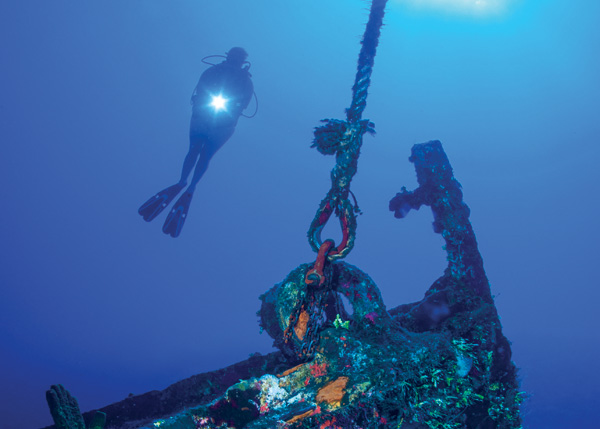 A photograph of a Diver and Wrecked Boat in the Turks and Caicos Islands.