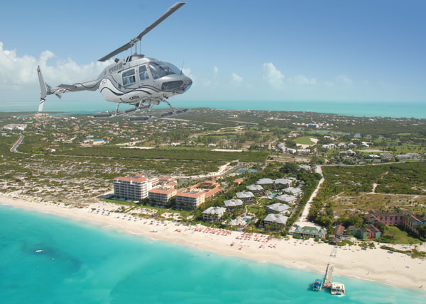 A photograph of a TCI Helicopters helicopter flying over the Turks and Caicos Islands