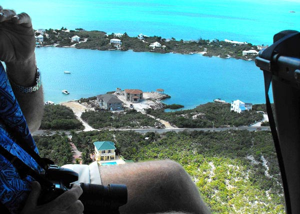 A photograph of a TCI Helicopters helicopter flying over Silly Creek, Providenciales (Provo), Turks and Caicos Islands